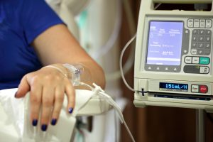 Infusion pump feeding IV drip into patients arm focus on needle